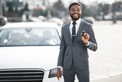 Car Owner. Happy African Businessman Showing New Auto Key Standing Near His Luxury Automobile Outdoors. Copy Space