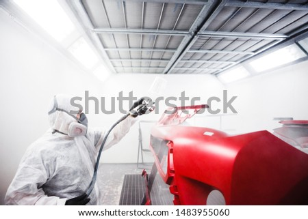 Car painter sprays varnish in paint booth. #1483955060