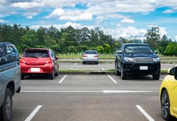 Car parked in asphalt parking lot and empty space parking  in nature with trees, beautiful cloudy sky and mountain background .Outdoor parking lot with fresh ozone and green environment concept