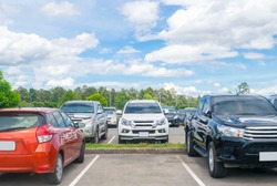 Car parked in asphalt parking lot and one empty space parking  in nature with trees, beautiful cloudy sky background .Outdoor parking lot with fresh ozone and green environment concept