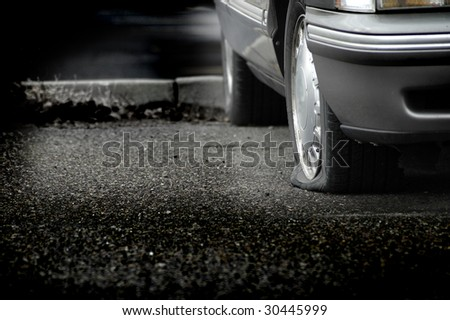 Car parked on a roadway with a flat tire