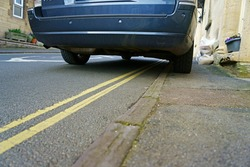 Car parked on double yellow lines and blocking the footpath by restricting access for pedestrians, Painswick, The Cotswolds, Gloucestershire, UK