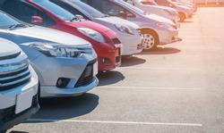 Car parking in asphalt parking lot in a row, front of  cars close up, automobile transportation dealer business concept