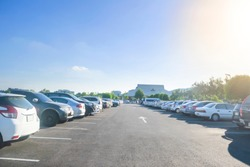 Car parking in large asphalt parking lot with trees, sunlight and blue sky background in front of hall building. Outdoor parking lot with fresh ozone and green environment concept