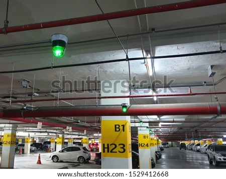 Car Parking lot sensor, Parking lot Guidance System with Overhead Indicators on ceiling that Indicator Light show Parking space unoccupied is green.