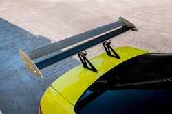 car part ; Close up detail of a custom racing carbon fiber spoiler on the rear of a yellow car