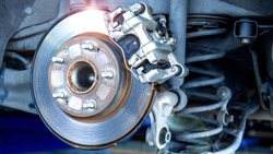 Car parts and disk brake concept - Closeup car disk brake maintenance service in car garage and copy spcae