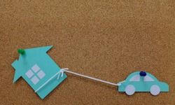 Car pulling a house model paper cutout. House as collateral property for auto loan