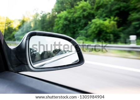 Car rear-view mirror on the motorway in summer in Germany with green trees in the background #1305984904