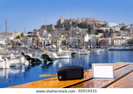Car rental keys on wood table with blank paper in Ibiza town Mediterranean island [ photo-illustration]