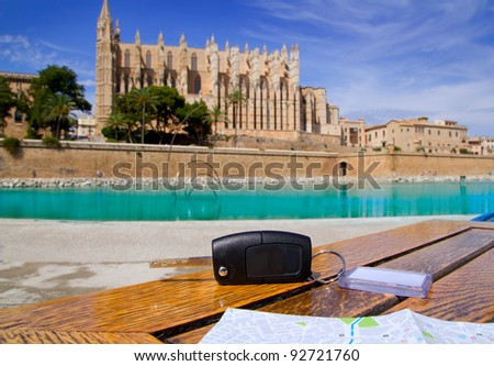 Car rental keys on wood table with city tourist map in Palma de Mallorca cathedral