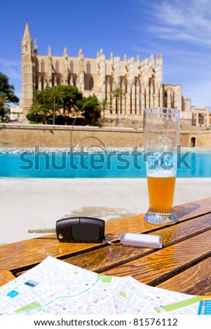 Car rental keys on wood table with city tourist map in Palma de Mallorca cathedral [Photo Illustration]