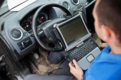 Car repair and maintenance theme. Electric mechanic in uniform working in auto service, making car diagnostics using obd device with laptop.