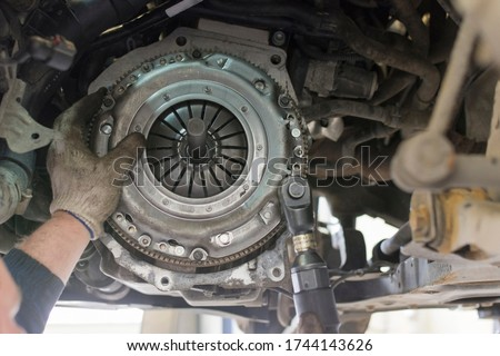 Car repair in a car service. Replacing the clutch disc of a gearbox on a car at a service station. Hands of a professional car mechanic. Cars repair technology. Technical photography.