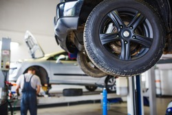 Car repair in the service station. Hands of a mechanic in overalls repairing the car on the lift without wheel, holding the tire and mechanical works.