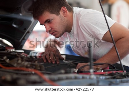 Car repair mechanic fixing auto. Man working on car in garage. At home do it yourself. Examine / inspect engine compartment for trouble; diagnose and fix / correct problem; preventative maintenance.