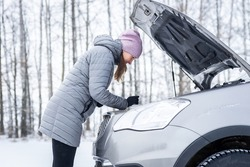 car repair on the road in winter. young girl is trying to fix a car breakdown under the soot on the road. woodsroadside assistance car