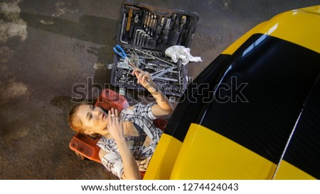 Car repair service. Sexy mechanic young woman lying under the car and holding an instrument #1274424043
