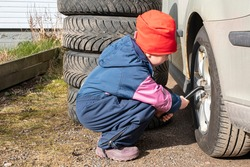 Car repair. The girl helps her parents with zeal. Girl changes wheels on a car.