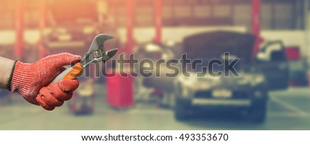 Car repairing,Hand of car technician auto mechanic with a wrench working in garage. Repair service in car repair station.vintage tone,for banner