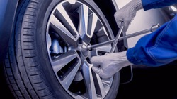 Car repairs. Replacing wheels. Seasonal tire replacement. The master removes the wheel with both hands with the key. A master in uniform. Part of the photo is blurry.
