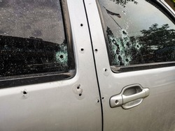 Car riddled with bullet holes .