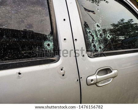 Photo of  Car riddled with bullet holes .