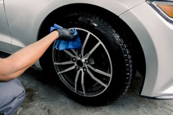Car rims cleaning, car detailing wash concept. Cropped close up photo of male hand in black rubber glove with blue microfiber cloth washing car alloy wheel at car wash service