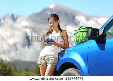 Car road trip woman driver eating lunch break outdoors in mountain landscape in Yosemite National Park, California, USA. Woman on summer holidays roadtrip vacation enjoying nature.