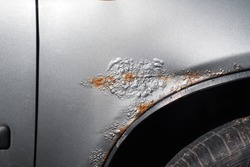 Car rust and corroded paint. Metal corrosion, cracked paint, holes in the car fender close-up. Part of an automobile body in metallic gray
