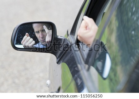 Car's side-view mirror reflecting male driver making obscene gestures. Horizontal shot.