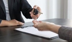 Car salesman gave the keys to the customers who signed the purchase contract legally, Successful completion of car sales, Purchase contract and key delivery.