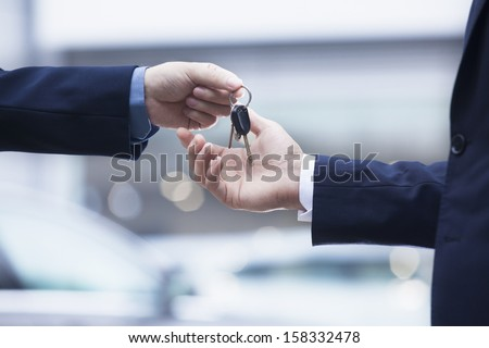 Car salesman handing over the keys for a new car to a young businessman ストックフォト ©