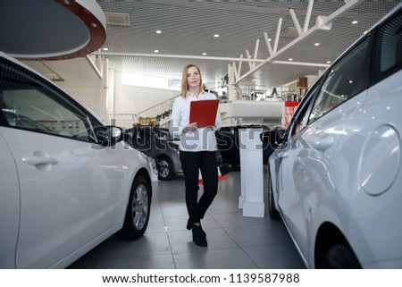 car salesman in a suit at the car showroom shows a beautiful elegant girl on a tablet information. Against the backdrop of saloon cars for sale or rental.