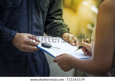 car salesman is making deal with lender. Used cars cheaper than new cars. But to buy a used car, the car must be thoroughly examined. Before lender signing deal leasing, the contract must be cautious. Stockfoto ©