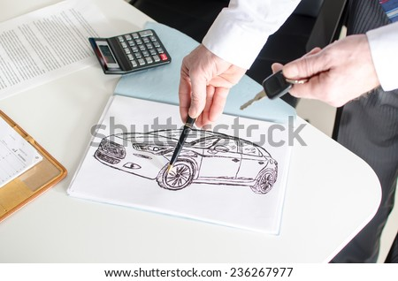 Car salesman showing a car design at the dealership office