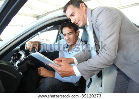 A customer signing a car rental agreement