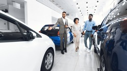Car Selling Business. Manager Showing Luxury Automobile To Afro Spouses In Automobile Dealership Center. Panorama
