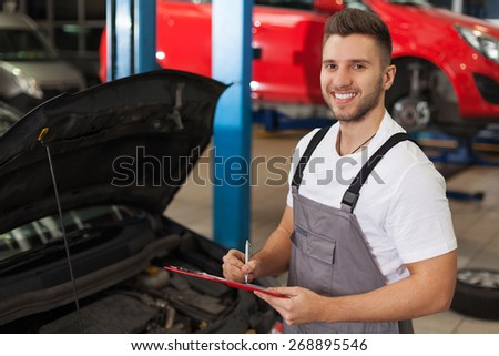 Car service inventory. Smiling mechanic in auto repair shop makes a note on a clipboard