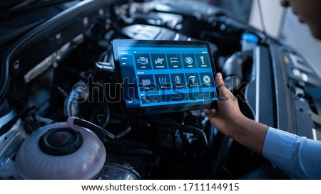 Car Service Manager or Mechanic Uses a Tablet Computer with a Futuristic Interactive Diagnostics Software. Specialist Inspecting the Vehicle in Order to Find Broken Components In the Engine Bay. Photo stock ©