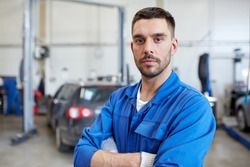 car service, repair, maintenance and people concept - auto mechanic man or smith at workshop