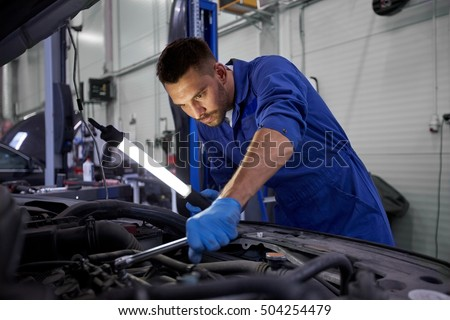 Shutterstock car service, repair, maintenance and people concept - auto mechanic man with lamp working at workshop
