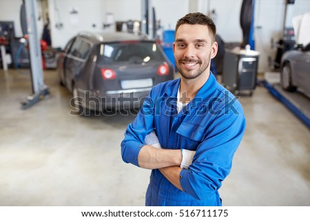 car service, repair, maintenance and people concept - happy smiling auto mechanic man or smith at workshop
