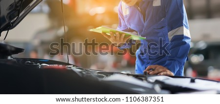 car service, repair, maintenance concept - Asian auto mechanic man or Smith writing to the clipboard at workshop warehouse, technician doing the checklist for repair machine a car in the garage,banner