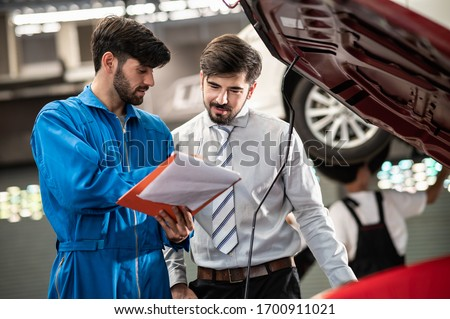 Car service, vehicle repair concept : Car service technician explaining checking list or repaired item to vehicle owner customer after sending car for repairing or check at automobile service center. Photo stock ©