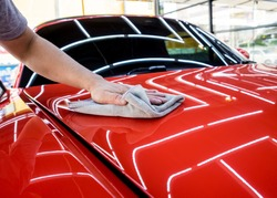 Car service worker polishing car with microfiber cloth.