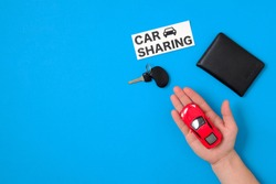 Car sharing concept with toy car in human hand, auto drive license, vehicle key, text sign