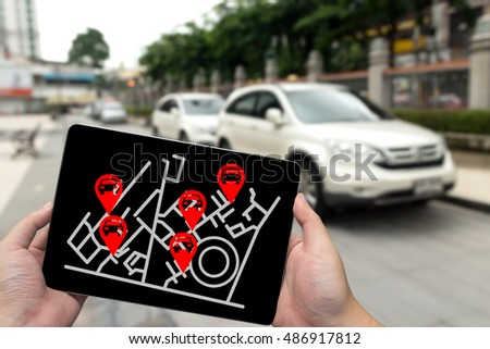 Car sharing service or rental concept. Sharing economy and collaborative consumption. Man hand holding tablet with icons application screen and blur car park background. Stock photo ©