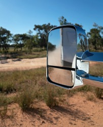 Car side mirror reflecting a blurred vision of a caravan traveling on a dirt road in the Australian outback