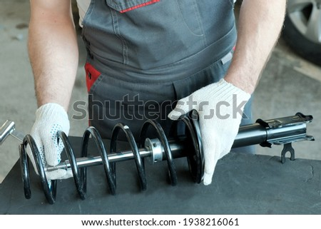 Car spare parts. Shock absorber strut and spring in the hands of a mechanic, close-up. Inspection of the compatibility of the spring part and the shock absorber strut.